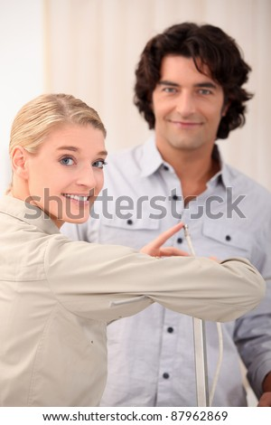 Woman pointing the end of a cable out to a man