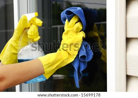 woman polishing glass door using microfiber cloth and yellow latex gloves