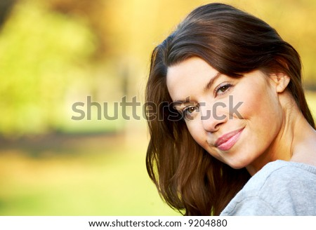 woman portirat smiling outdoors on a sunny day