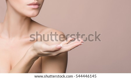 Woman Portrait. Beautiful Spa Girl showing empty copy space on the open hand palm for text. Proposing a product. Skin Care Concept. on pink with clipping path