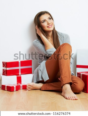 Woman portrait in christmas style with red, white box gift seat, isolated on white background.