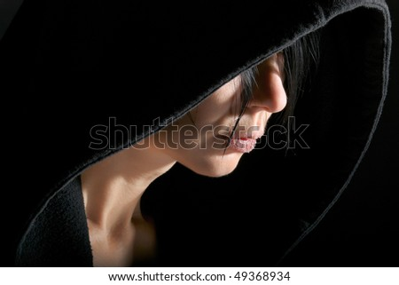Woman portrait in low key with contour from hood