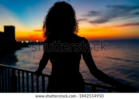 Woman portrait silhouette facing the sea at sunset. Real lifestyle image. Stock photo ©