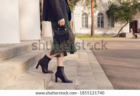 woman pose in black ankle boots with mini bag on the stairs, street style outfit Foto stock ©
