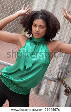 Woman posing by the fence