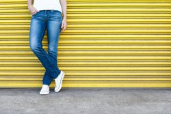 Woman posing in jeans against garage door.