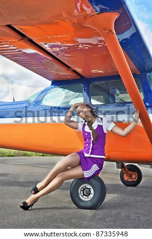 Woman posing near airplane