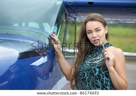 Woman posing near airplane outdoor