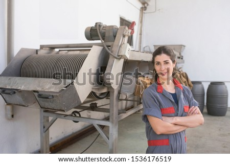 Woman posing near to machine conveyer belt for olives packaging #1536176519