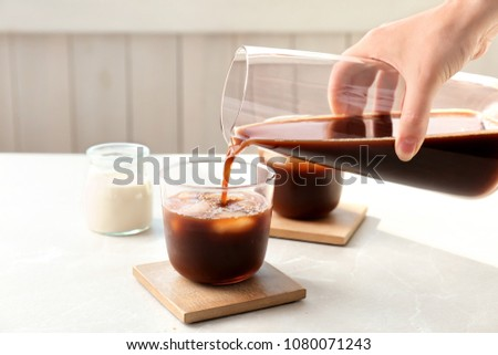 Woman pouring cold brew coffee into glass on table