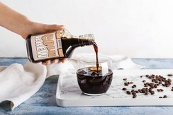Woman pouring cold brew from bottle into glass on table