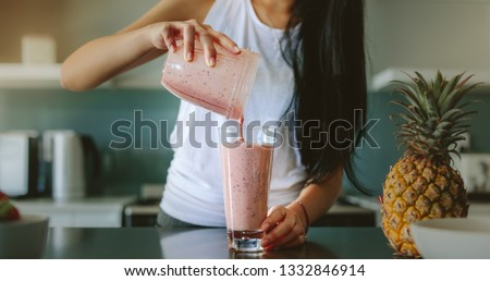 Woman pouring healthy smoothie in glass from grinder jar on kitchen counter. Female preparing fresh fruit smoothie in her kitchen with pineapple on the counter.
