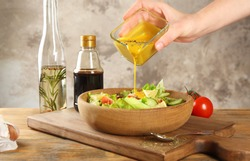 Woman pouring honey mustard dressing into bowl with fresh salad on table