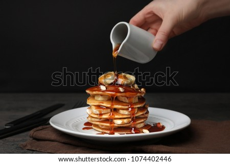 Woman pouring maple syrup on tasty pancakes #1074402446