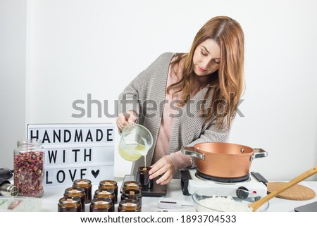Woman pouring melted wax into amber candles container. Ecological and vegan business. Soya wax candle accessories. Handmade with love. Remote work, online shop, workplace