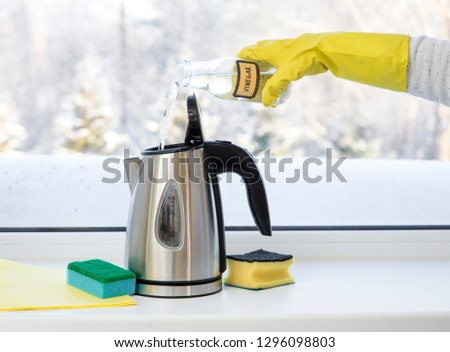 Woman pouring natural destilled acid white vinegar in electric kettle to remove boil away the limescale. Descaling a kettle, remove scale concept.