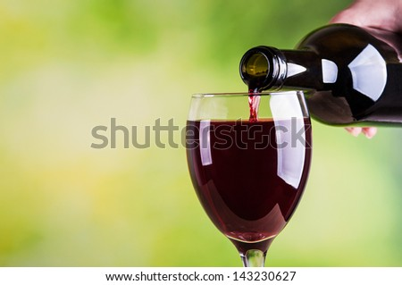 Woman pouring red wine into glass