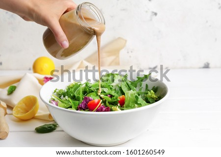 Woman pouring tasty tahini from jar onto vegetable salad in bowl Foto stock ©
