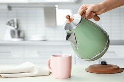 Woman pouring water from modern electric kettle into cup at wooden table in kitchen, closeup