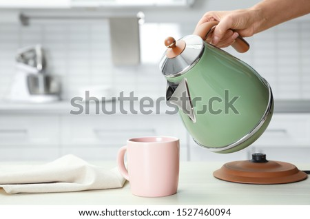 Woman pouring water from modern electric kettle into cup at wooden table in kitchen, closeup Stock photo ©