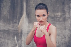 Woman power, self defence concept. Close up portrait of attractive serious fit boxer, ready for fight, on concrete wall background, wearing pink fashionable sport wear