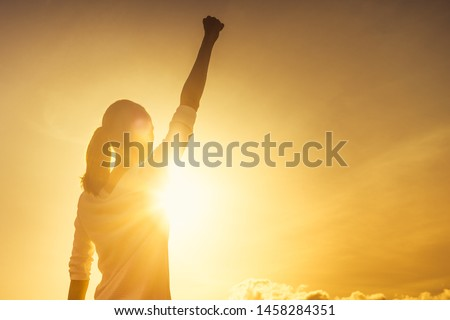 Woman power, victory and winning concept. Woman with fist in the air at sunset.