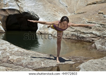 Woman practices yoga along side  the solitude of a remote swimming pool in the Yosemite wilderness on a sunny afternoon.