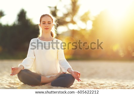 Shutterstock woman practices yoga and meditates in the lotus position on the beach