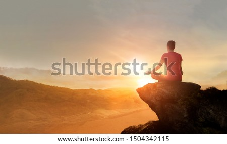Woman practices yoga and meditating on the mountain sunset background.