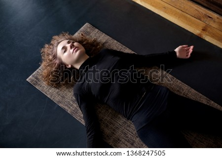 woman practicing in a yoga studio resting in shavasana or corps pose Foto stock ©
