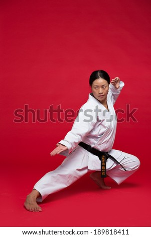 Woman practicing karate on red background