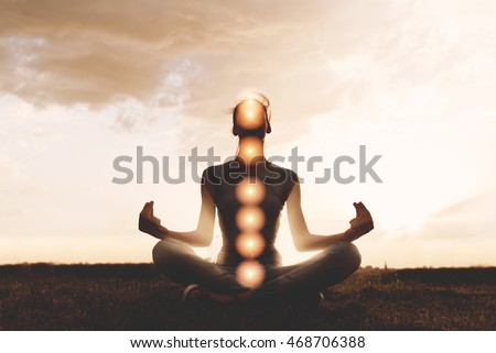 Woman practicing meditation in sunset, with chakras marked #468706388