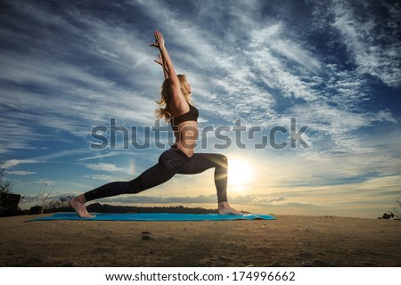 Woman practicing Warrior yoga pose outdoors over sunset sky background
