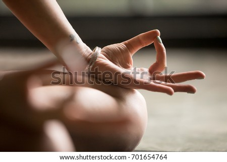 Photo of Woman practicing yoga at home. Jnana mudra close up, female, connecting the thumb and forefinger, forming a circle, palms facing upwards, harmony and concentration yoga concept, focus on left hand