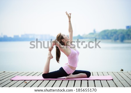 woman practicing yoga at seashore