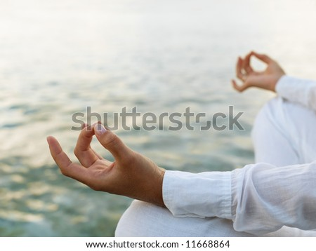 Woman practicing yoga at sunrise near the ocean