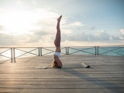 Woman practicing yoga at sunrise on pier over the sea enjoying nature and relaxation. Female holding inversion yoga pose headstand upside down requiring balance