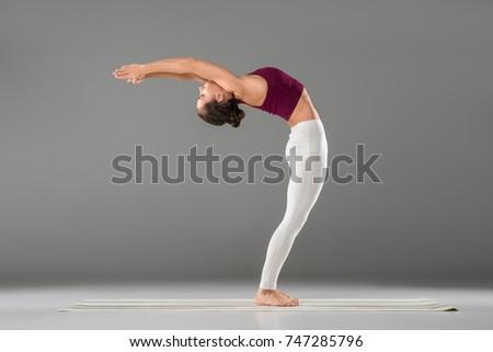 woman practicing yoga, doing Standing Backward Bend exercise, Ardha Chakrasana pose