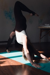 Woman practicing yoga in the studio, face downward dog pose. Yoga concept, healthy lifestyle, stretching