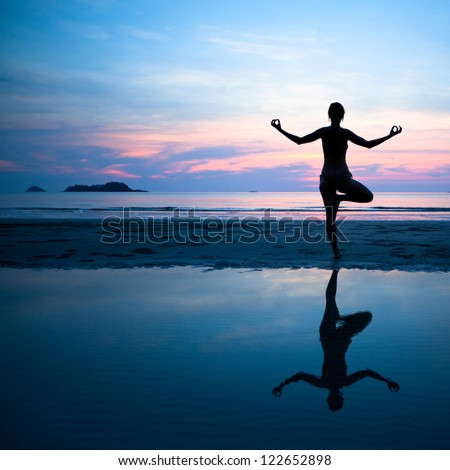 Woman practicing yoga on the beach after sunset