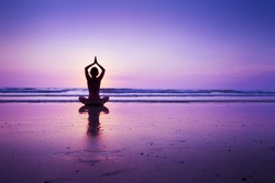 Woman practicing yoga on the beach at sunset in Koh Chang, Thailand