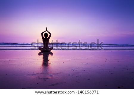 Woman practicing yoga on the beach at sunset in Koh Chang Thailand