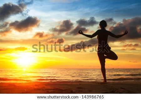 Woman practicing yoga on the beach, during sunset.