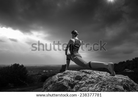 Woman practicing yoga pose outdoors over sunset sky background. Fitness classes outdoors