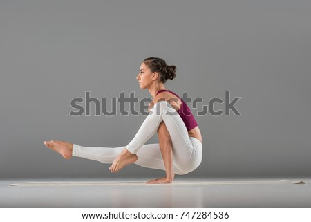 Shutterstock woman practicing yoga, standing in Leg over shoulder, Elephant Trunk exercise, Eka Hasta Bhujasana pose