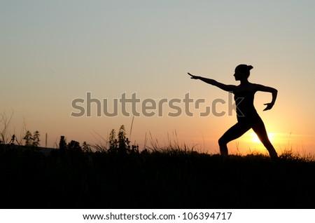 Woman praticing tai chi chuan at sunset.