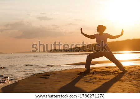 Woman praticing tai chi chuan at sunset on the beach. Chinese management skill Qi's energy. solo outdoor activities. Social Distancing   Сток-фото ©
