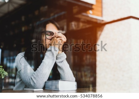 Woman pray with bible, Asian woman  believe in the  prayer to God, Christian student pray for study to pass the exam in the library at the college .Bible and christian study concept - Shutterstock ID 534078856