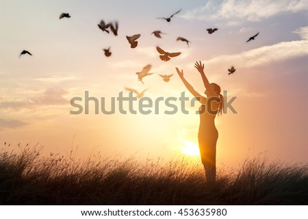 Shutterstock Woman praying and free bird enjoying nature on sunset background, hope concept