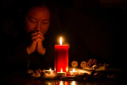 Woman Praying and worship to GOD Using hands to pray in religious beliefs and worship christian with Red Candle with fire against defocused lights in darkness with in the dark Background